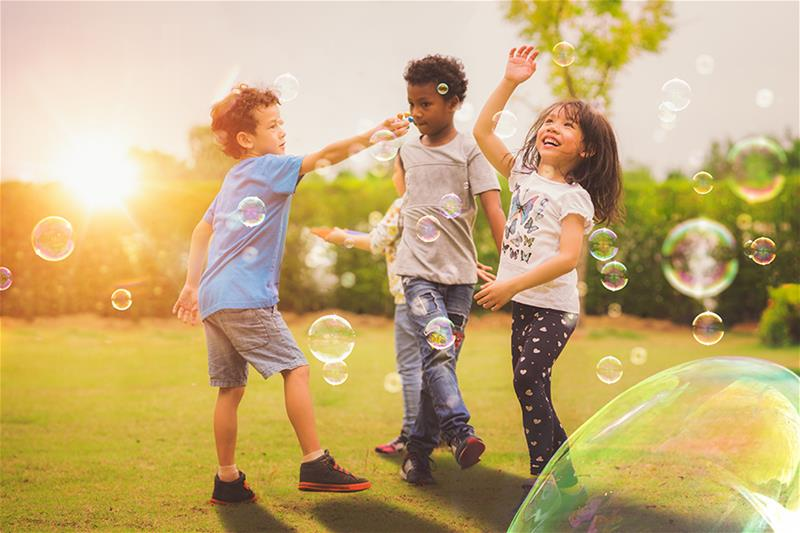 Diverse group of kids playing with bubbles