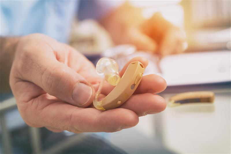 Man holding a hearing aid out to show someone