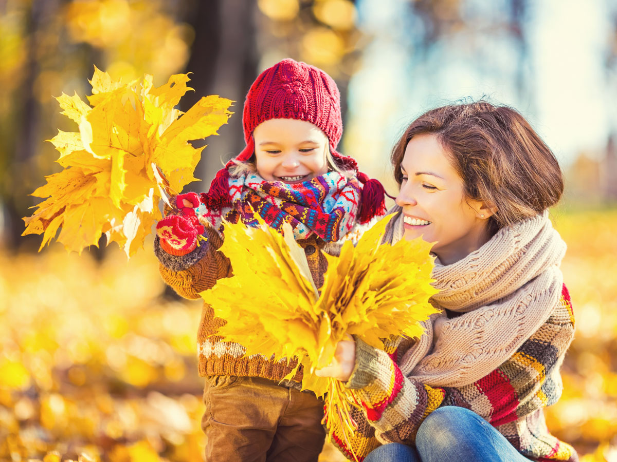Mom and child gathering fall leaves
