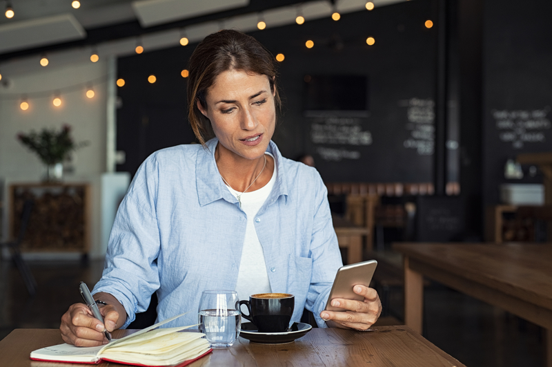 Woman in coffee shop planning with her smartphone