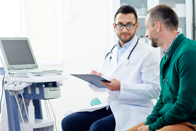Doctor consulting with a male patient in the exam room