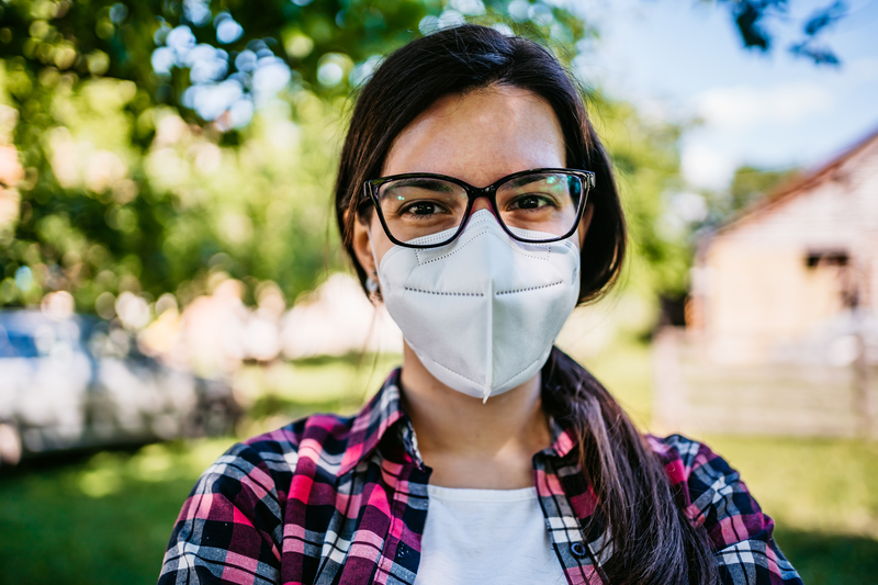 Young woman with mask wearing glasses